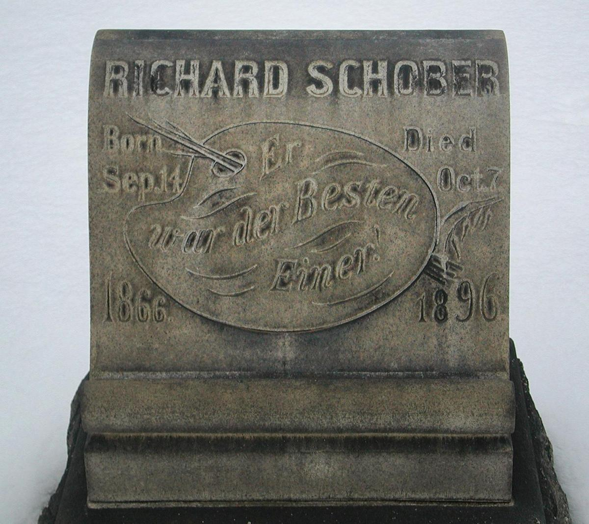 Photo shows a gray headstone in the snow. It is decorated with an artist's tools, a man's name at the top, dates, and text in German.