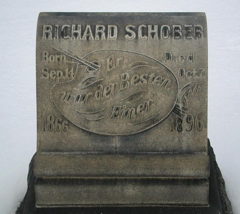 Photo shows a gray headsstone in the snow. It is decorated with an artist's tools, a man's name at the top, dates, and text in German.