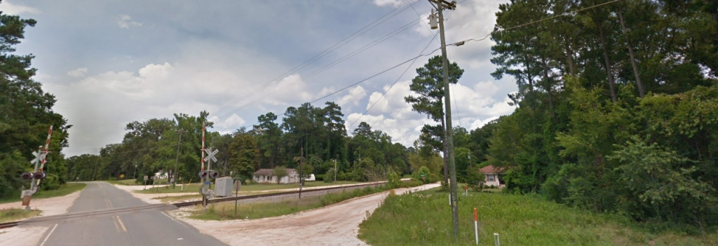 Paved and gravel roads. Train crossing and small homes among trees. Blue skies.