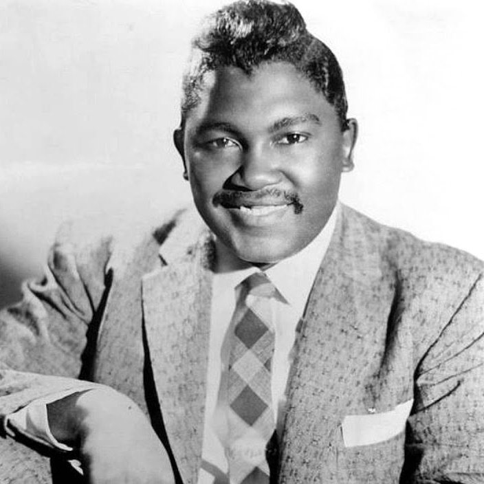 Photo of an African American man from the 1950s. Suit and tie. Pomaded hair, a pocket square, and a smile.
